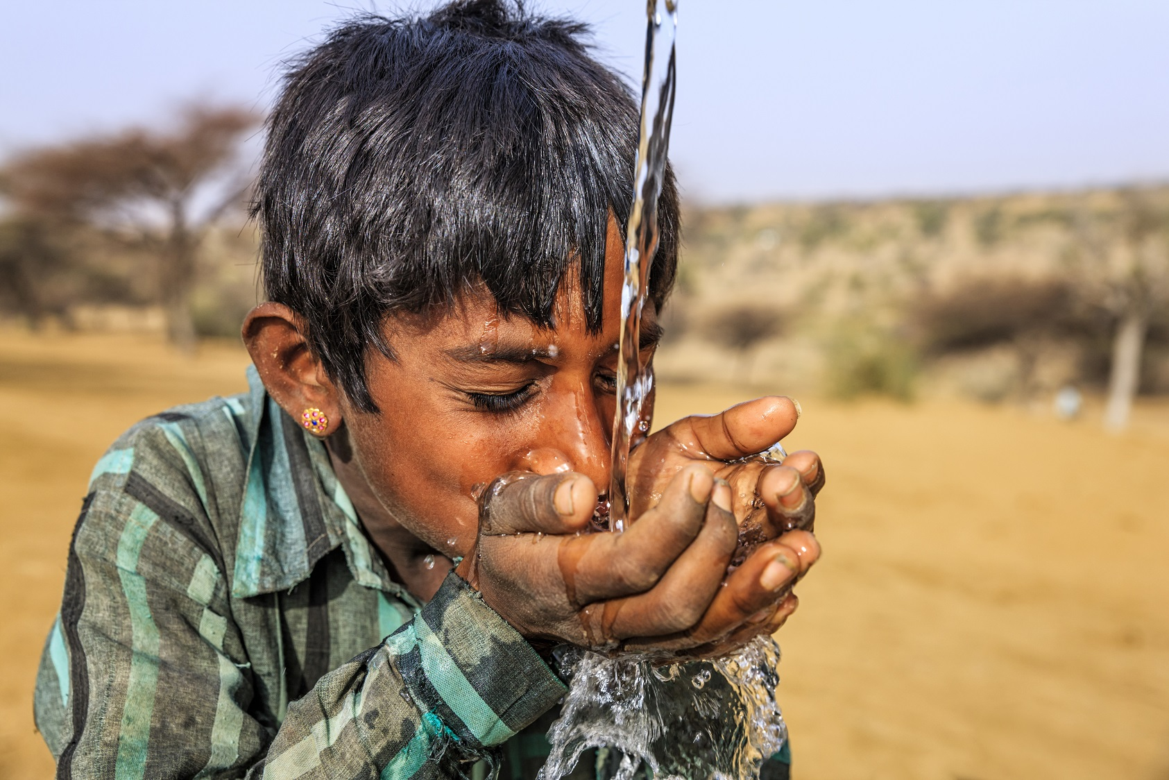 Image of young Indian boy catching clear water in his hands and drinking