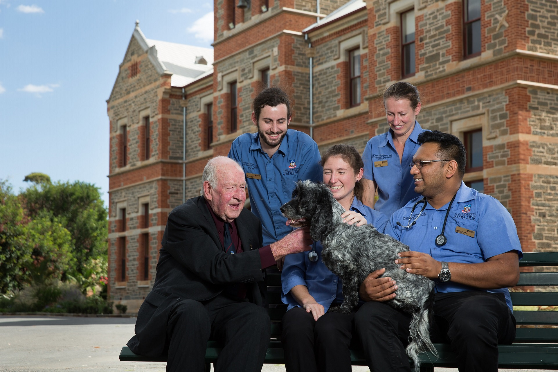 Image of Graham Smith sitting outside Roseworthy campus with some veterinary science students and a happy dog