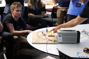 University of Adelaide student Luke Heffernan, getting a closer look at a simple burn-wire mechanism, used to deploy solar panels and antenna from a micro-satellite in orbit.