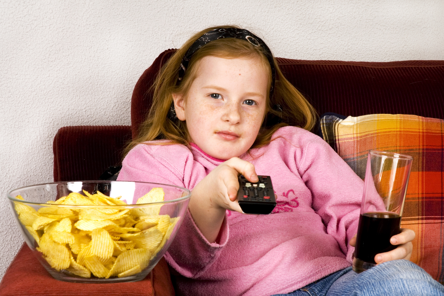 Child eating chips watching television