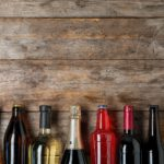 various alcohol bottles against wooden backdrop