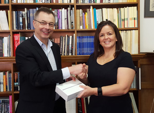 Photo of Stacey receiving her brand new iPad mini from Paul Wilkins.