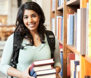 A shot of a student holding books at the library